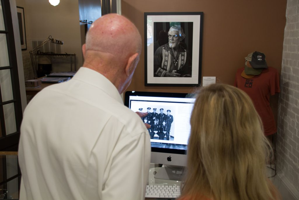 A man pointing to a black and white photo on the screen of an iMac to identify police officers pictured in the image as a female employee of the W7thCo Gallery takes notes.